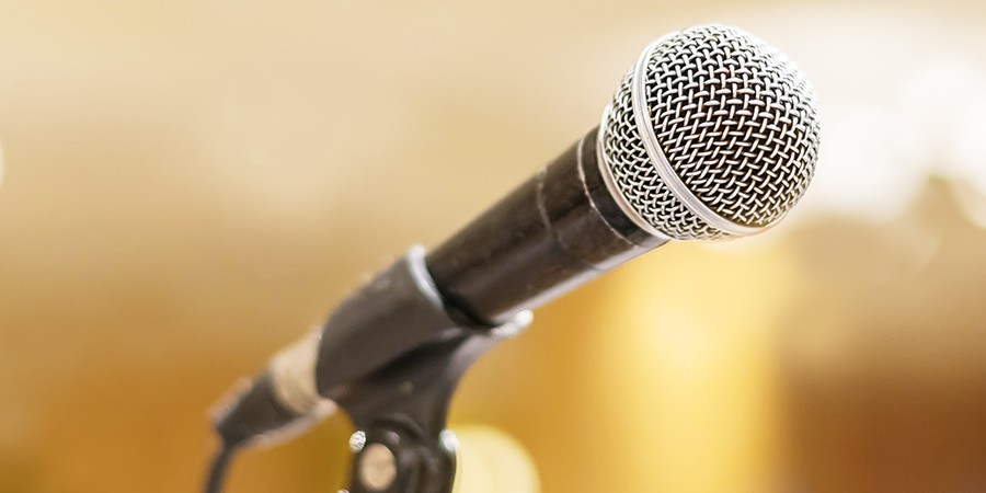 microphone in concert hall or conference room with lights in background. with extremely shallow dof..