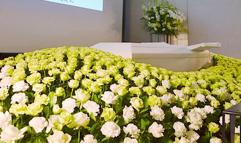 お柩の周りに黄色と白のバラを